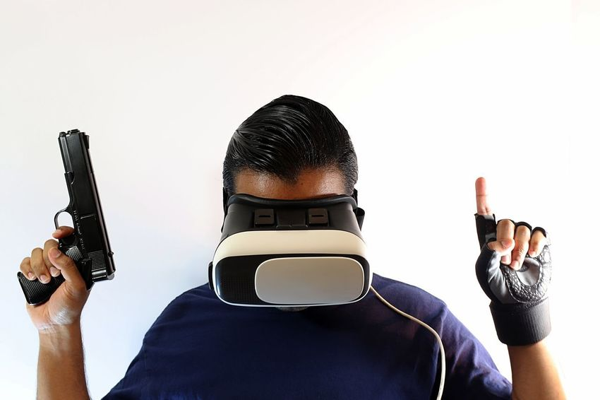 Young man with virtual reality headset holding gun and wearing gloves while pointing up and looking down Console Display Futuristic Gamer Gaming Glasses Gloves Goggles Gun Headset Innovation New Pistol Playing Riffle Role Playing Game Shooter Shooting Technology Virtual Virtual Reality War Weapon White Background Wireless Technology