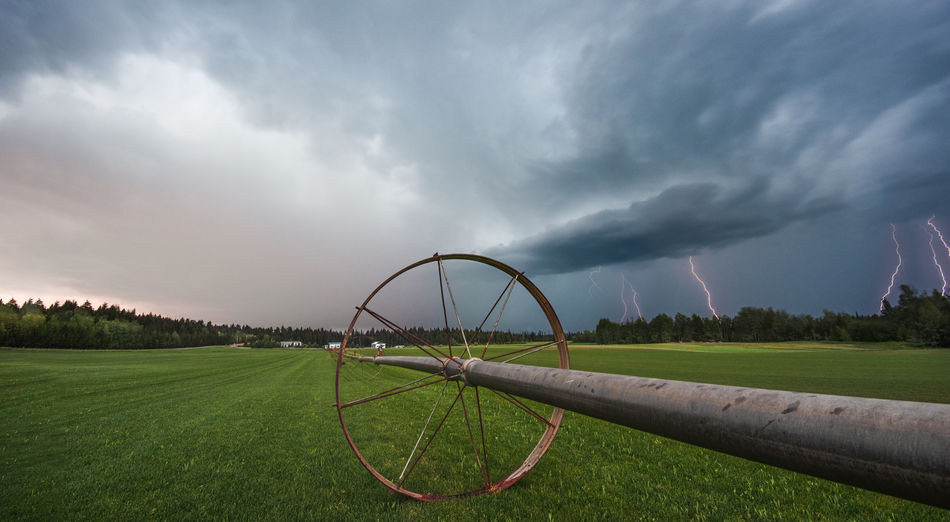 A lightning storm over a farm Farm Circle Cloud - Sky Day Environment Field Grass Green Color Land Landscape Lightning Metal Nature No People Outdoor Play Equipment Outdoors Overcast Plant Scenics - Nature Shape Sky Storm Storm Cloud Turf Wheel