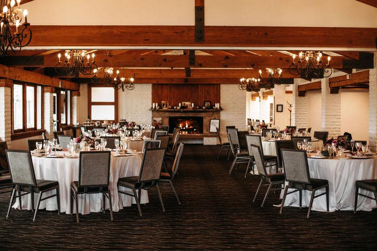 Beautiful wedding venue with white table cloths, glassware, floral arrangements center pieces