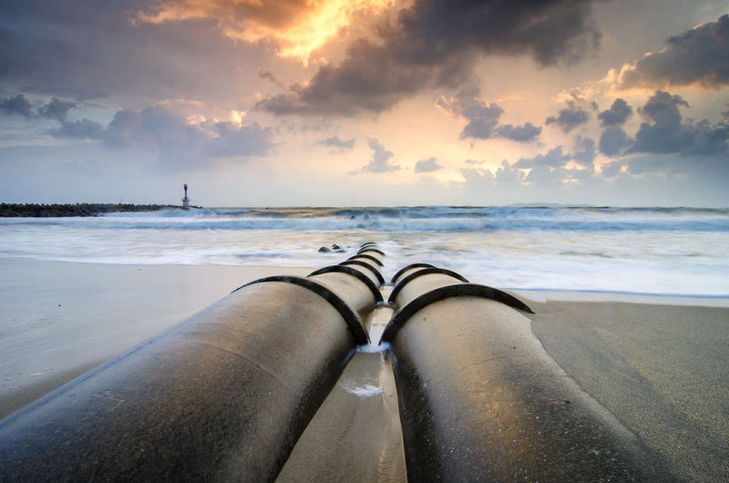 Pipes At Beach Against Sky During Sunset