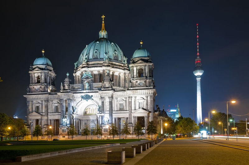Illuminated berlin cathedral and fernsehturm against sky at night