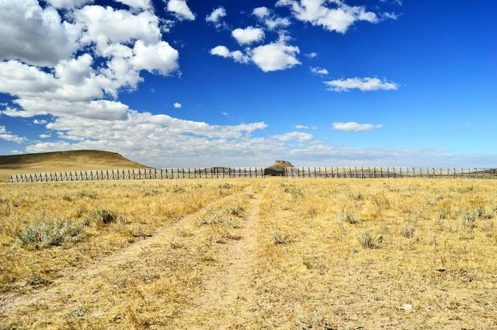 Trail road Ground Dirt Pasture Hills Sunshine Shadow Outdoors Clouds And Sky Yellow Color Grass Snow Fence Blue Landscape