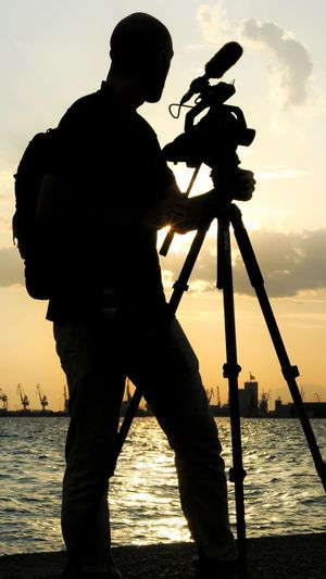 silhouette of a young male operating a camera on a tripod during sunset Videographer Young Male Thessaloniki Waterside Camera Operating Video Camera Camcorder Equipment Tripod Water Full Length City Sunset Standing Silhouette Sky Photographic Equipment
