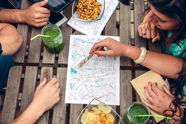 High Angle View Of Friends Discussing On Map While Sitting In Restaurant