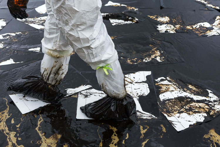 Low section of man walking on oil spill