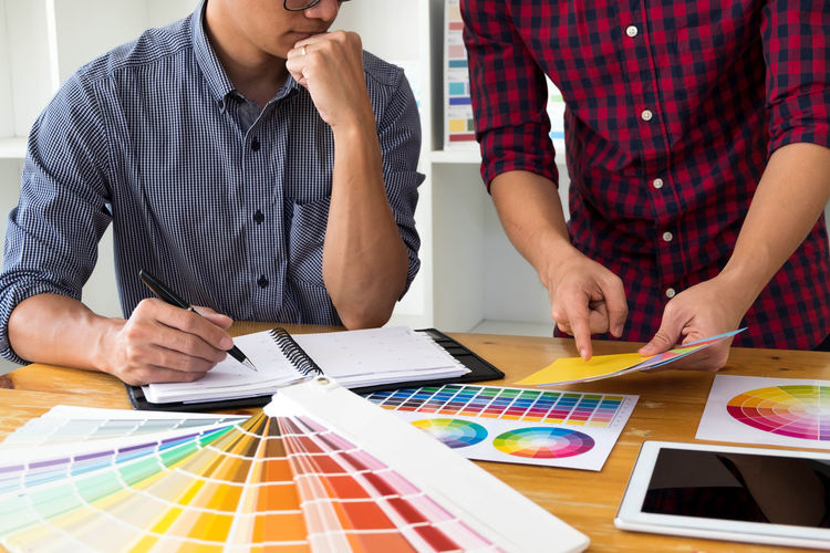 Midsection of colleagues with color swatches and note pad working on desk
