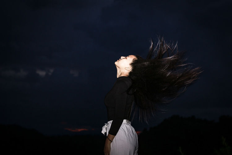 Side view of woman tossing hair standing outdoors at night