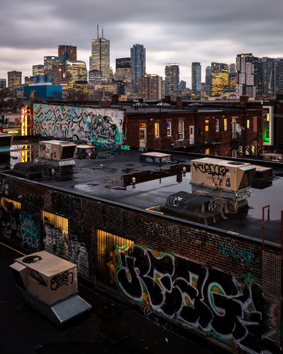 Dark and brooding skyline of Toronto-- shot in the early evening from Kensington Market over graffiti-lined rooftops Building Exterior Architecture Built Structure City Sky Building Cloud - Sky Cityscape Transportation No People Office Building Exterior Outdoors Urban Skyline High Angle View City Life Skyscraper Modern Kensington Market  Graffiti Gritty City Landscape Decayed Beauty New And Old Architecture Age Contrast Brick Wall