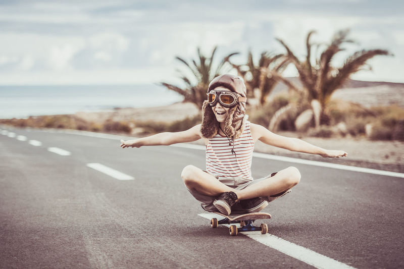 Cheerful boy sitting on skateboard against sky