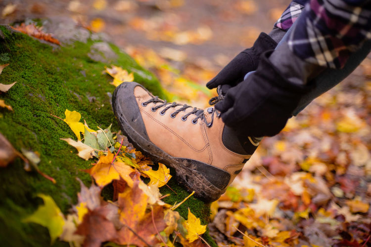 Low section of man wearing autumn leaves on field