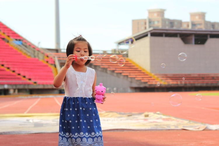 Portrait of girl blowing bubbles