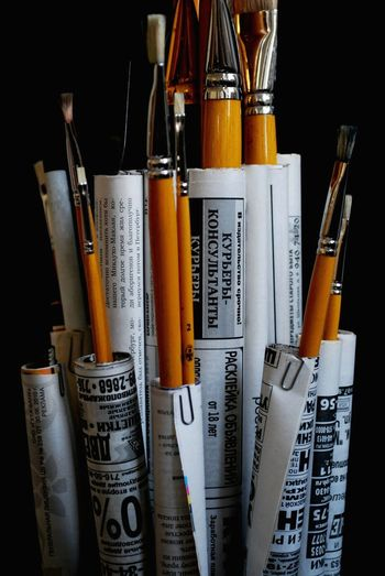 Paintbrushes with papers against black background