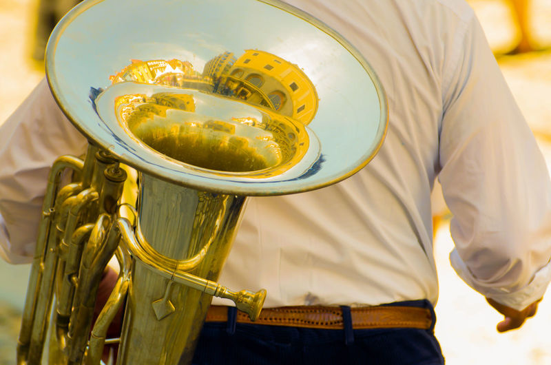 City of Locarno Reflected in a Musical Instrument in Switzerland. City Rear View Reflected  Reflection Sunny Arts Culture And Entertainment Brass Instrument  Building Exterior Built Structure Day Gold Colored Holding Men Midsection Music Musical Instrument Musician One Person Outdoors Real People Standing
