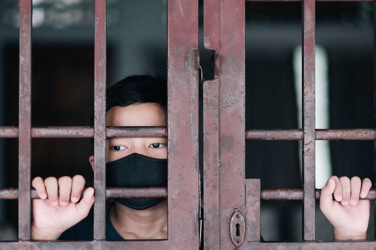 Boy wearing mask standing behind metallic door