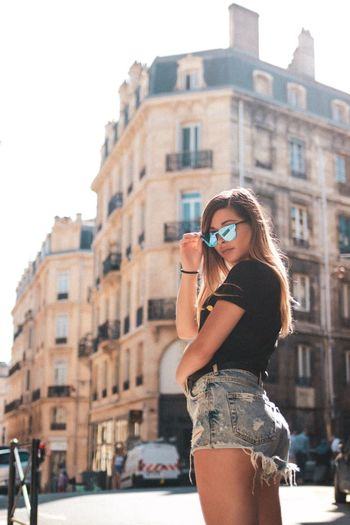 Side view portrait of woman standing against buildings in city during sunny day
