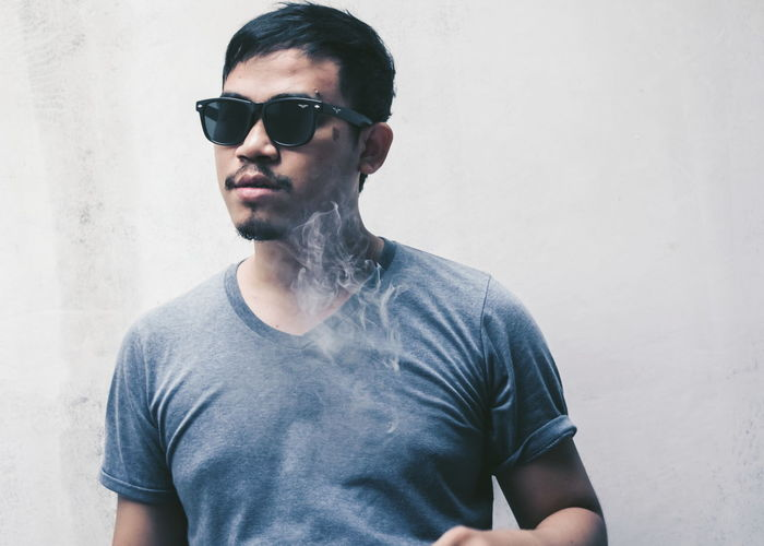 Young man smoking while standing with sunglasses by white wall