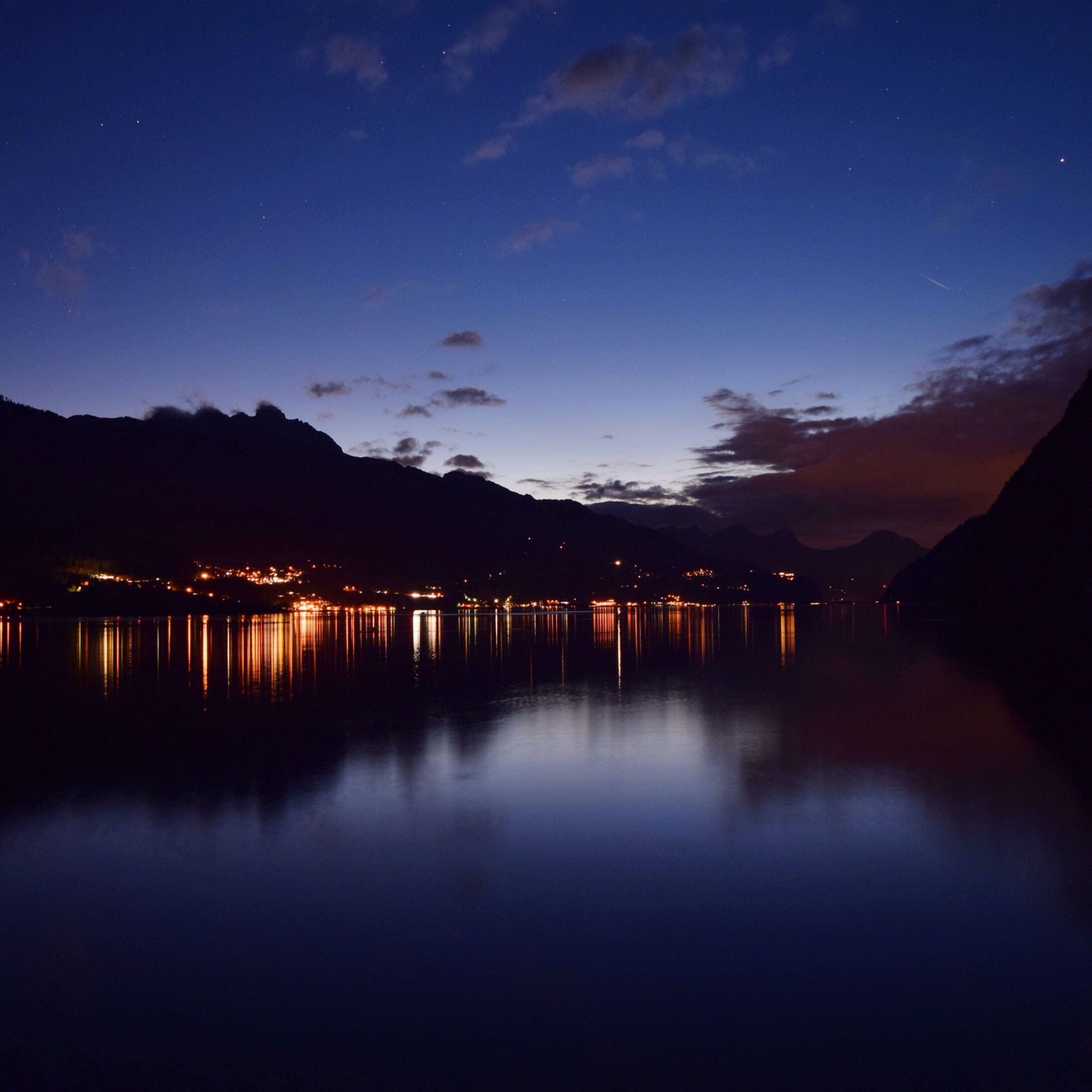 reflection, water, illuminated, tranquil scene, tranquility, lake, sky, waterfront, night, scenics, beauty in nature, dusk, mountain, built structure, silhouette, nature, idyllic, standing water, sunset, architecture