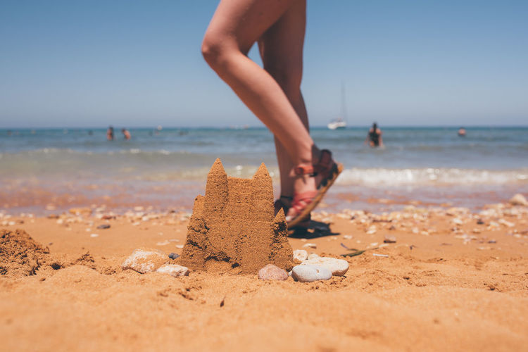 Low section of woman walking on beach against sky