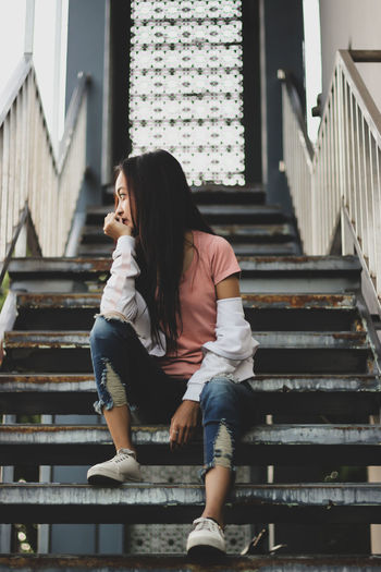 Thoughtful woman sitting on staircase