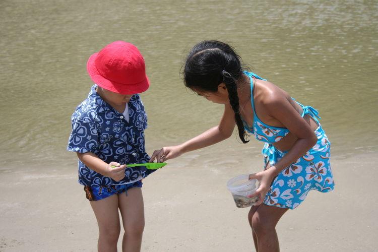 Siblings Playing At Beach