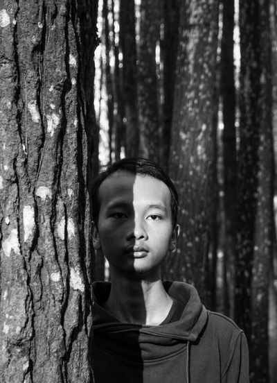 Portrait of young man by tree trunk in forest