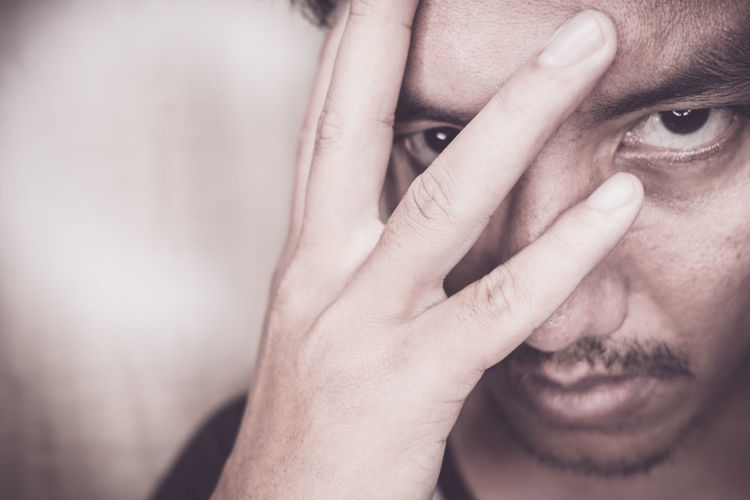 Close-Up Portrait Of Angry Man With Hand Touching His Face