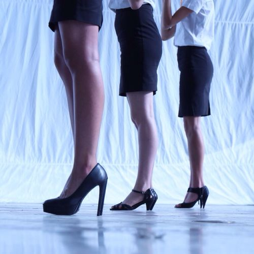Low section of women wearing mini skirt and high heels