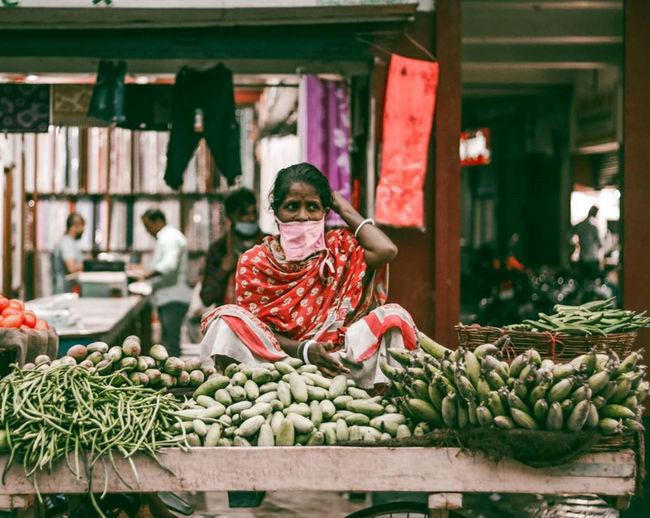 Portrait of boy in basket at market stall