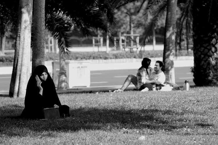 Boys Covered Day Full Length Grass Growth Hijab Hijabstyle  Leisure Activity Lifestyles Men Nature Outdoors Palm Tree Park - Man Made Space Real People Sitting Togetherness Tree Tree Trunk Tschador Women Young Adult Young Women çador EyeEmNewHere The Photojournalist - 2018 EyeEm Awards