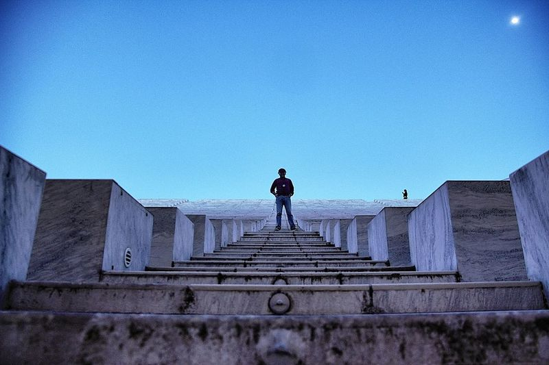 Low Angle View Of Man Standing On Steps Against Clear Blue Sky