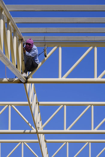 Low angle view of man walking on metallic structure against blue sky
