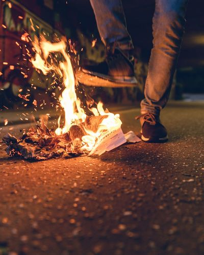 Low section of man standing by burning papers on street at night