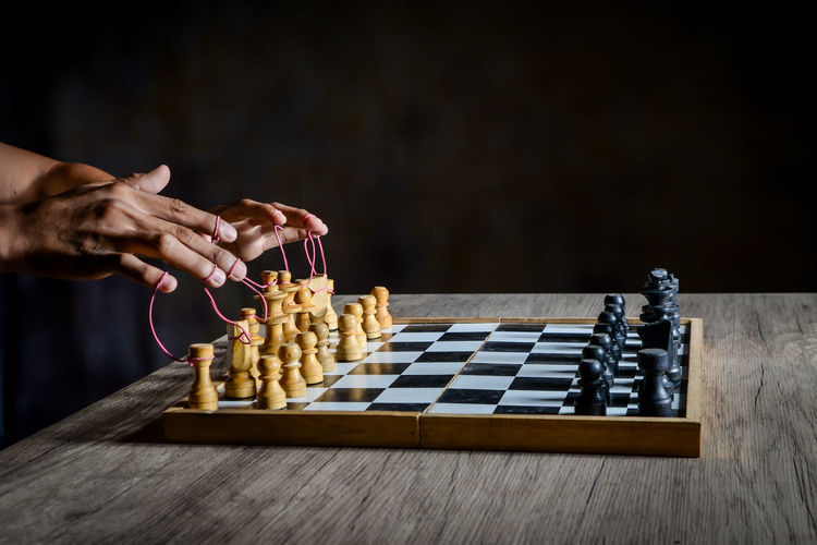 Low angle view of person playing on chess board