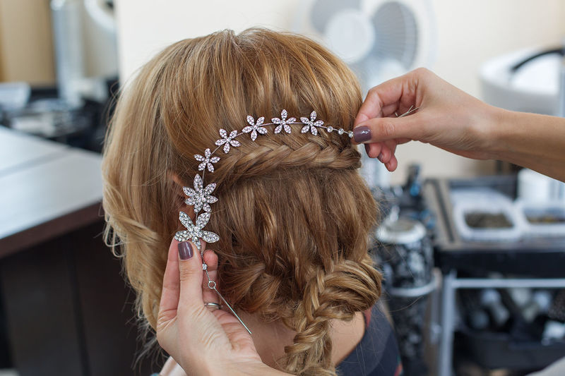 Cropped Hands Of Beautician Putting Tiara On Bride Hair At Spa