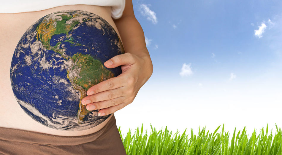 Midsection of pregnant woman with planet earth on stomach against sky