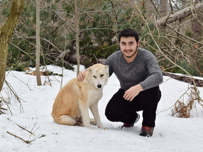 Portrait of young man smiling while crouching with dog on snow covered field