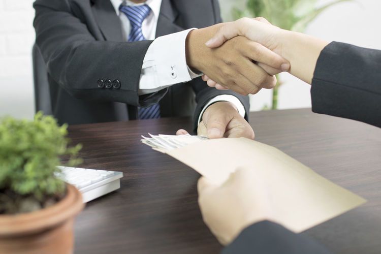 Midsection of businessman shaking hands while accepting bribe