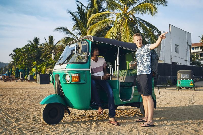 Tuk tuk driver with passenger against sand beach and sea in Sri Lanka. Sri Lanka Beach Driver Occupation TukTuk Taxi Sand Men Talking Passenger Travel Transportation Direction Service Visit Journey Real People Palm Tree Lifestyles Two People Positive Emotion Backpacking Vacations Tourism Tropical Climate