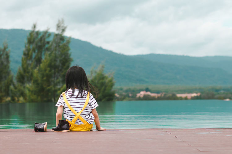Beauty In Nature Casual Clothing Child Childhood Day Full Length Hairstyle Lake Leisure Activity Lifestyles Mountain Nature One Person Outdoors Real People Rear View Scenics - Nature Sitting Water Women