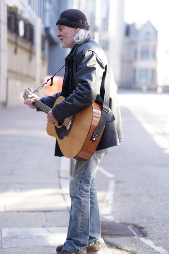 Side view of man playing guitar on street