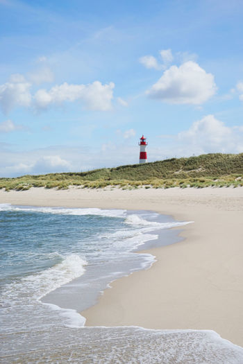 Sand beach landscape with lighthouse in the back Water Land Cloud - Sky Sky Beach Sea Lighthouse Nature Day Safety Outdoors Lighthouse Ellenbogen, Sylt Clouds And Sky Waves Sunny Day Springtime