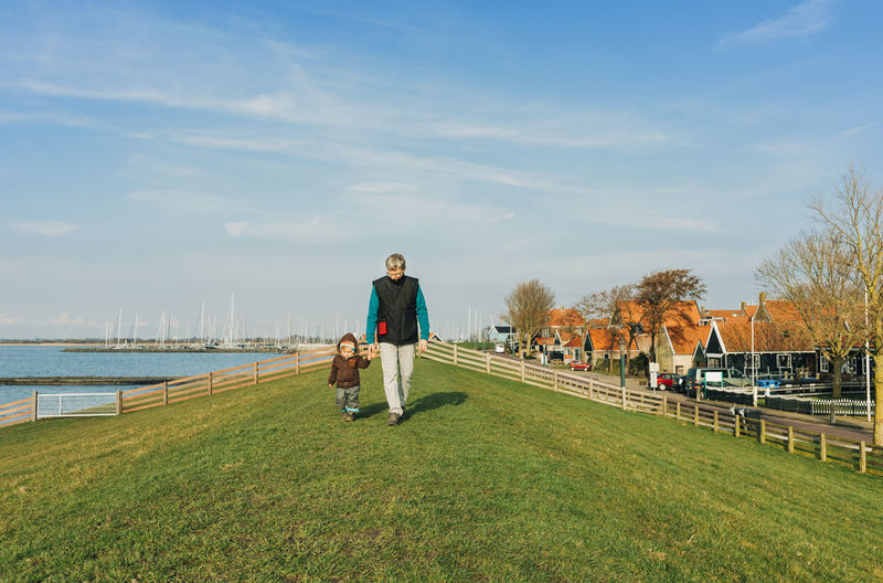 Man with toddler walking on dyke – Hindeloopen, Netherlands, Europe Ijsselmeer Mature Adult Mature Men Grandfather Grandchild Granddaughter Multi-generation Family Family With One Child Family Family❤ Two People Child Childhood Generations Childhood Memories Girl Baby Care Holding Hands First Steps Walking Hiking Wanderlust Hikingadventures Dyke  Netherlands Front View Exploring Happiness Hindeloopen Friesland Lake Love Offspring Patience Slow Toddler  Toddlerlife Togetherness Vacations Shore Fence House Town Village Roof Distant Side By Side Footpath Sunset Grass Sky Real People Plant Nature Day Full Length Casual Clothing Water Lifestyles Leisure Activity People Men Adult Sunlight Land Green Color Cloud - Sky Outdoors