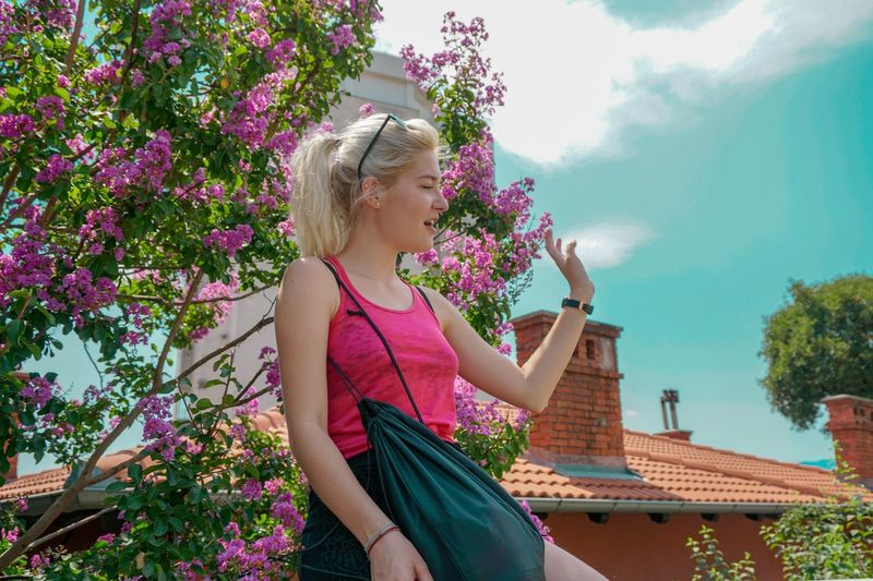 Woman waving while standing by pink flower