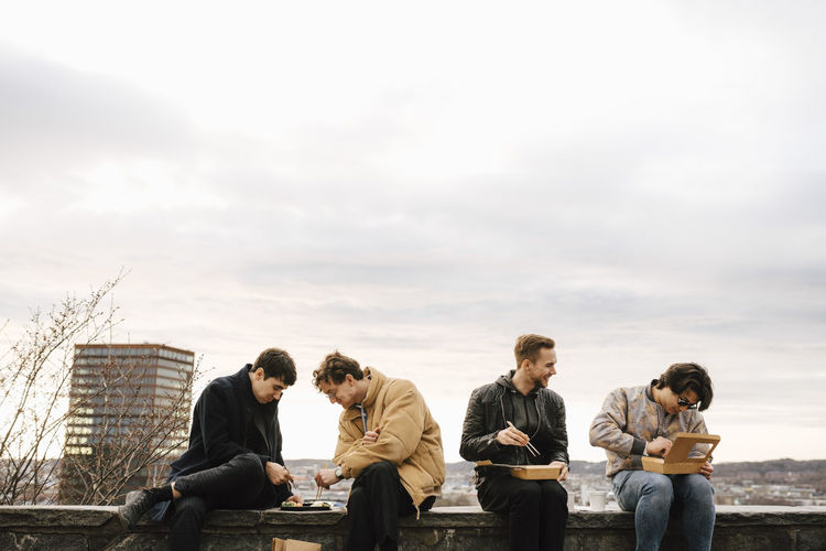 Group of people sitting against sky