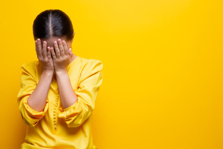 Woman covering face against yellow background