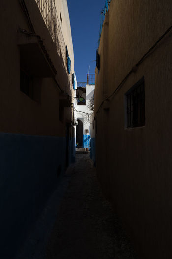 Alley amidst buildings against clear sky