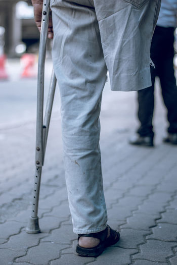 Low section of disabled man standing on footpath in city
