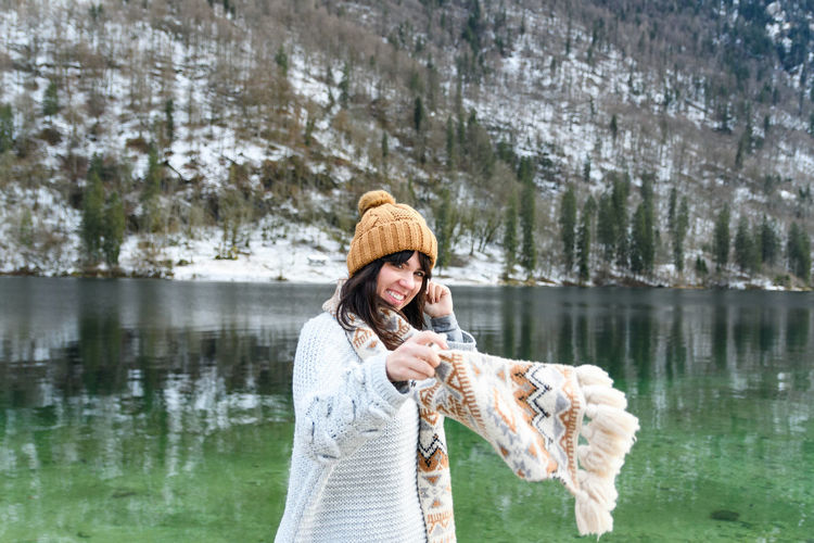 Young woman in winter sweater smiling, standing by a lake.