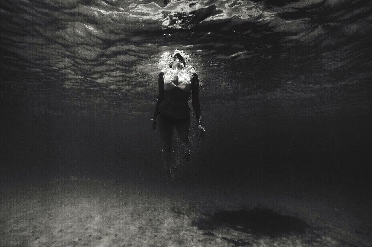 YOUNG WOMAN STANDING IN WATER