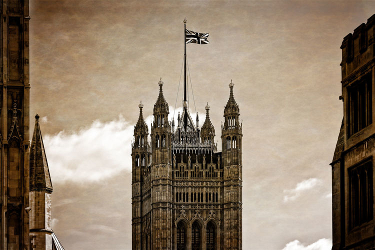 Low angle view of westminster abbey and buildings against cloudy sky